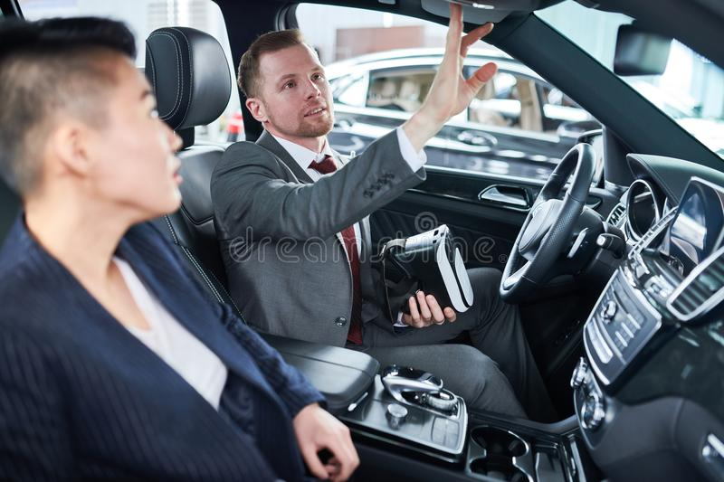 Showing Car to Potential Customer. Handsome young car dealer wearing classical suit holding VR headset in hands while showing new automobile model to potential stock photo