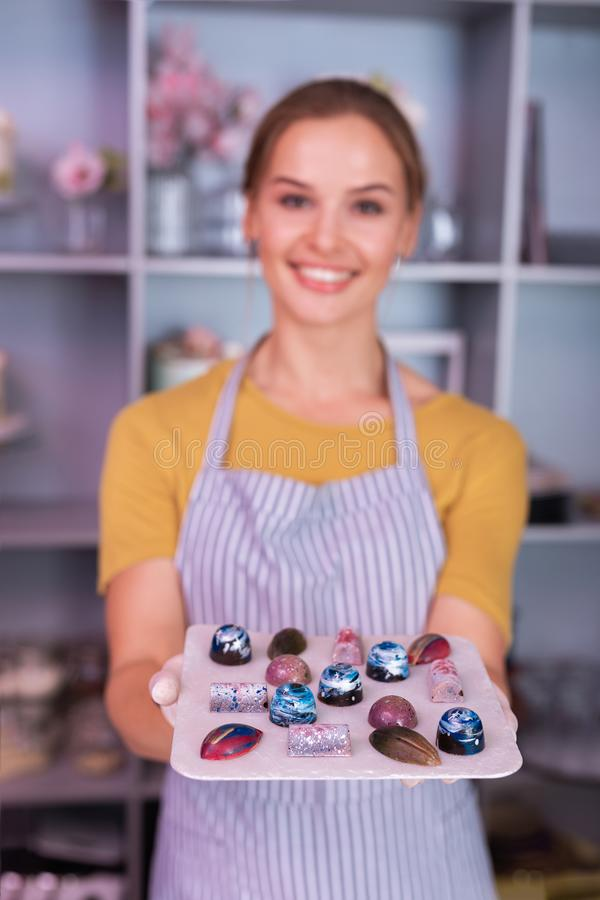 Smiling young chocolatier showing her perfect colorful chocolates. Showing chocolates. Smiling young chocolatier feeling excited while showing her perfect stock photography