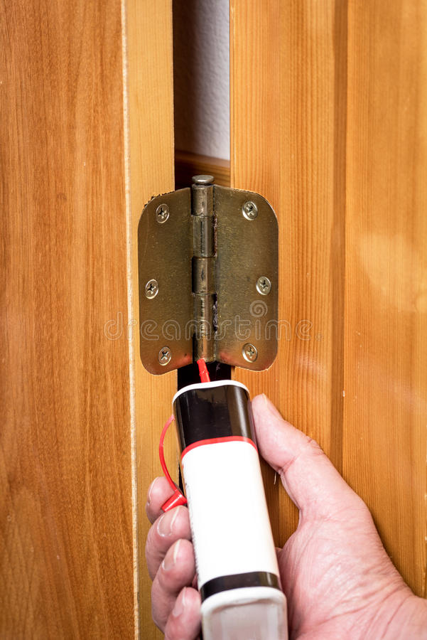 Showing how to properly oil a door hinge. Demonstrating a door hinge getting some oil royalty free stock photo