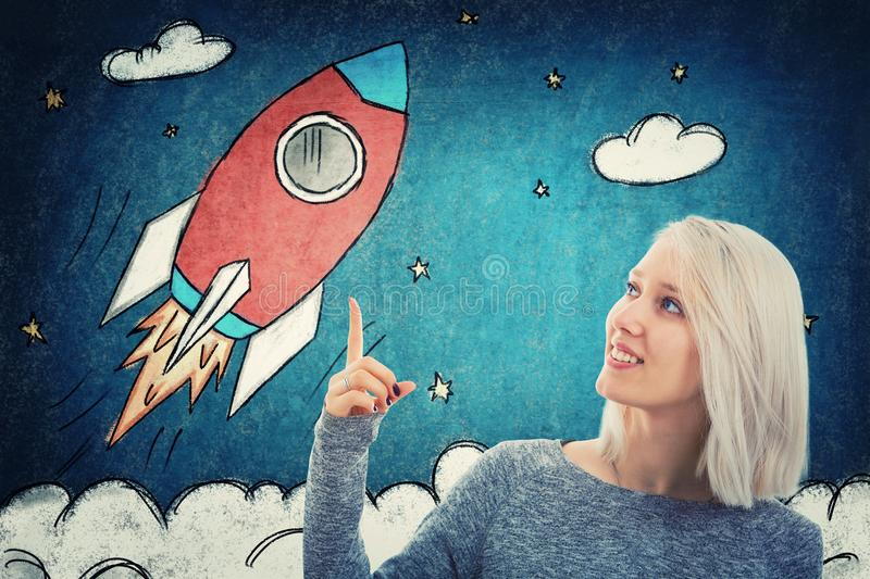 Showing with the index finger. Portrait of smiling student girl pointing her finger up, showing a drawn rocket ship take off in space. Business launch and royalty free stock image