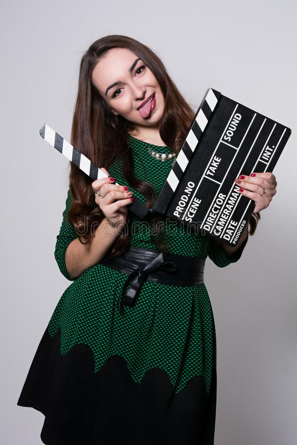Showing the language young woman holding a movie clapper. Girl in green dress helps in shooting a movie royalty free stock image