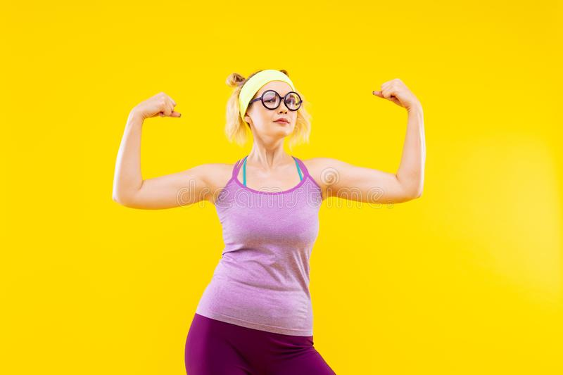 Blonde-haired woman wearing glasses showing her muscles royalty free stock image
