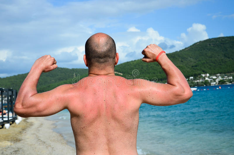 Showing muscles. Strong man showing muscles in a Vacation holiday resort complex in Bodrum ,Turkey royalty free stock photography
