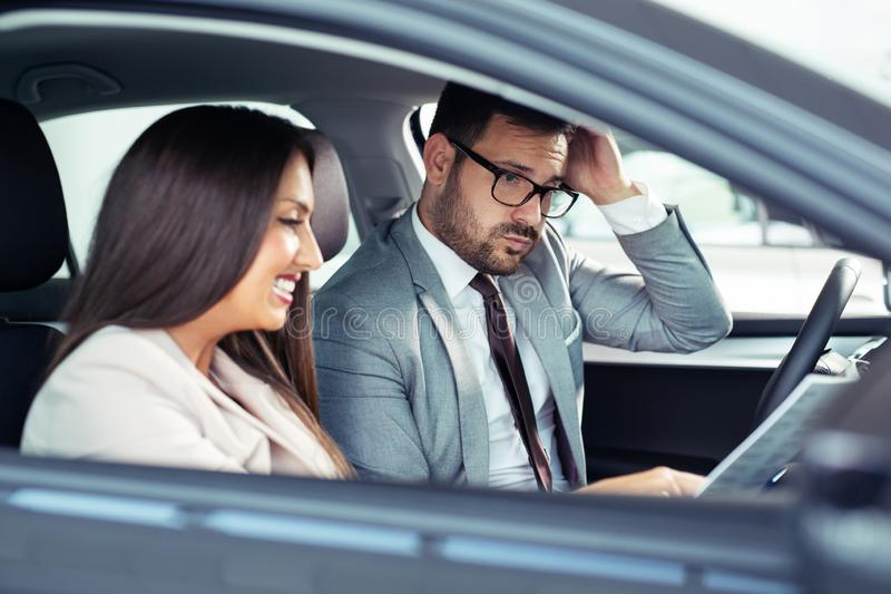 Showing car brochure to a customer in car showroom royalty free stock photo