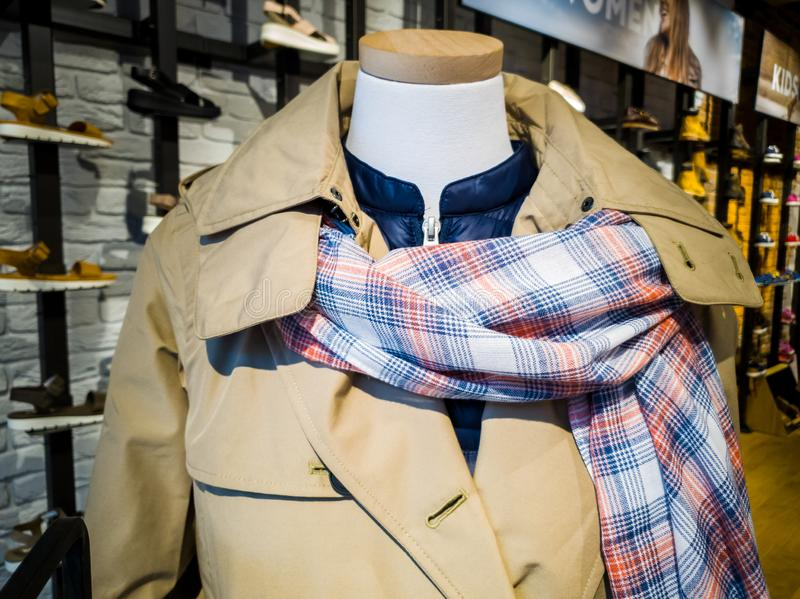 A mannequin displays the latest fasionable scarf, mac and jacket in a store royalty free stock photos