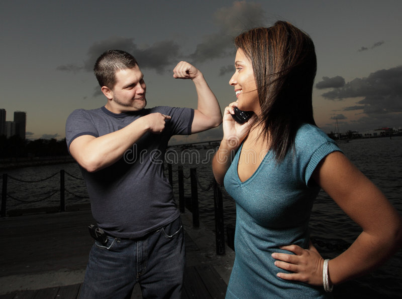 Showing off the muscles. Young man showing off hi muscles to the woman royalty free stock photography