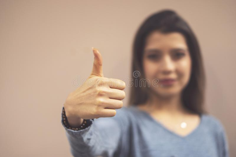 Showing okay gesture and people concept - happy smiling young woman or teenage girl royalty free stock image