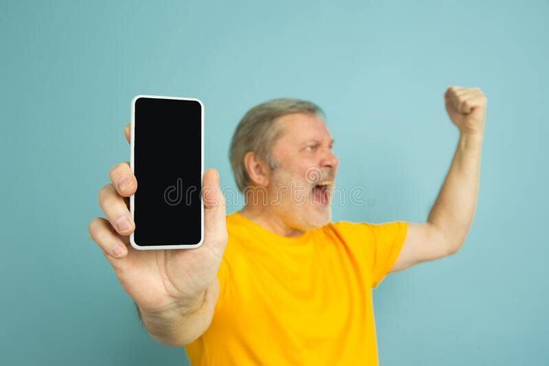 Caucasian senior man`s portrait isolated on blue studio background royalty free stock images