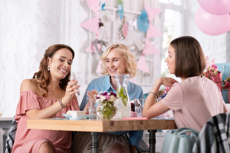Pregnant family woman showing her wedding photos her colleagues. Showing photos. Pregnant family women feeling proud while showing her wedding photos her royalty free stock images
