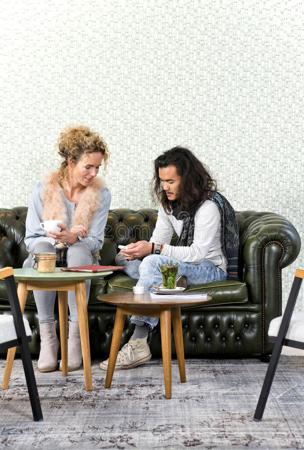 Showing smartphone photos. Young men showing a women a few photos on his smart phone, sitting on a luxurious couch in a retro styled lounge stock photos