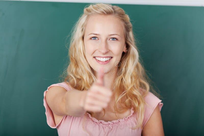 Showing Thumbs Up för kvinnlig student tecken arkivfoto