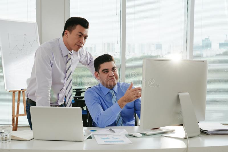 Showing work. Businessman showing his work to Vietnamese coworker royalty free stock images