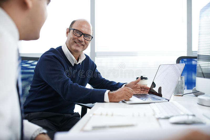 Showing work. Cheerful businessman sharing his work with colleague royalty free stock photos