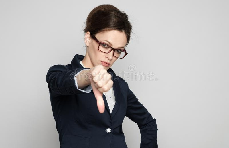 Showinh sérieux de femme d'affaires son themb vers le bas photo libre de droits