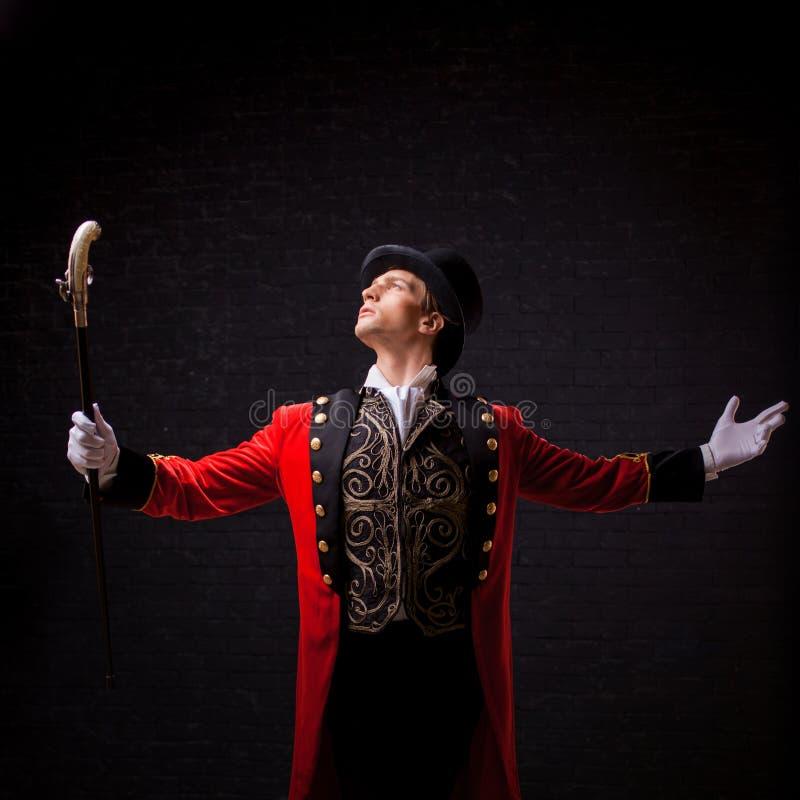showman Молодые мужские эстрадный артист, вручитель или актер на этапе Парень в красном лифчике и цилиндре стоковая фотография
