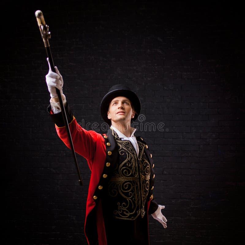 showman Giovane anfitrione, relatore o attore maschio in scena Il camisole del tipo in rosso ed il cilindro immagine stock