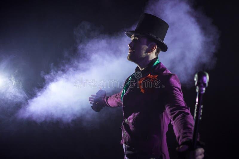 showman Jonge mannelijke entertainer, presentator of acteur op stadium De kerel in purpere camisole en de cilinder stock afbeelding