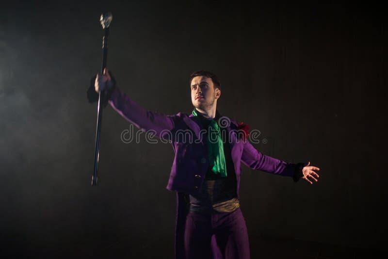 showman Jonge mannelijke entertainer, presentator of acteur op stadium De kerel in purpere camisole en de cilinder stock foto