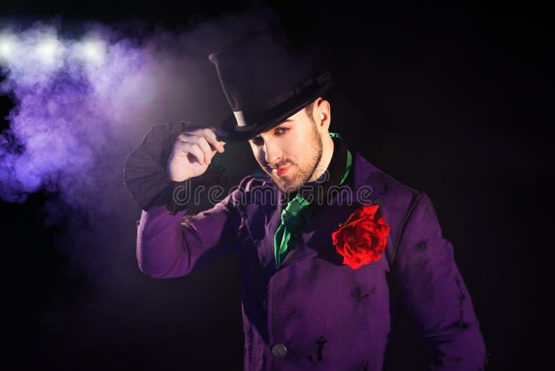 showman Jonge mannelijke entertainer, presentator of acteur op stadium De kerel in purpere camisole en de cilinder royalty-vrije stock afbeeldingen