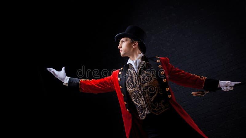 showman Jonge mannelijke entertainer, presentator of acteur op stadium De kerel in rode camisole en de cilinder stock foto
