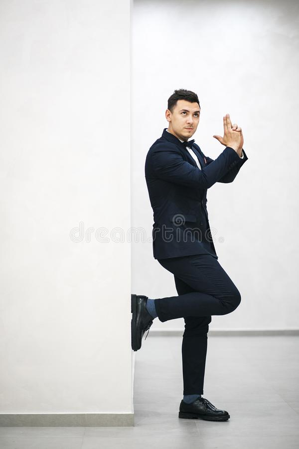 Showman posing with arms folded like a gun. The showman poses with his arms folded like a gun, he rolls his eyes up, standing on one leg royalty free stock photography
