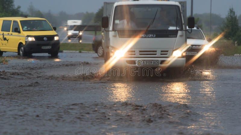 SHPOLA UKRAINA JULI 28, 2017: bilkörning på en översvämmad väg under en flod som orsakas av hällregn, i Shpola arkivfoton