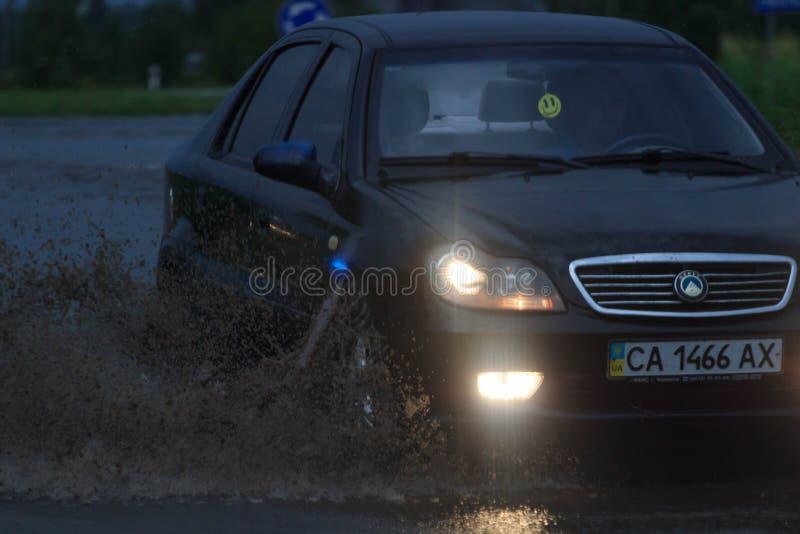 SHPOLA, UKRAINE 28 JUILLET 2017 : entraînement de voitures sur une route inondée pendant une inondation provoquée par la forte pl photographie stock