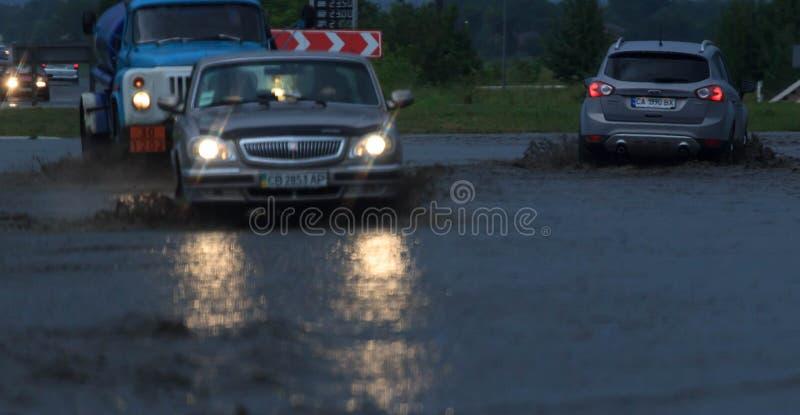 SHPOLA, UKRAINE 28 JUILLET 2017 : entraînement de voitures sur une route inondée pendant une inondation provoquée par la forte pl image libre de droits