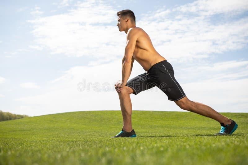 Shredded парень работает на траве в парке стоковое фото