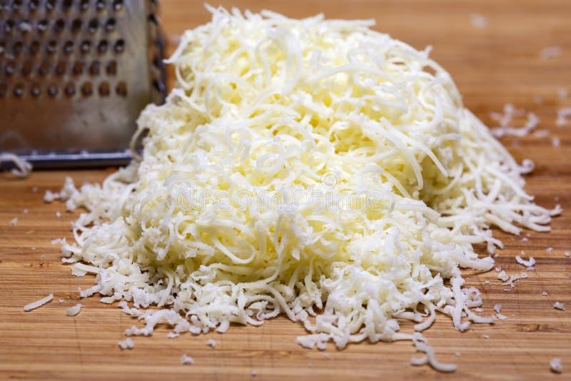 Shredded mozzarella cheese on a cutting board stock photos