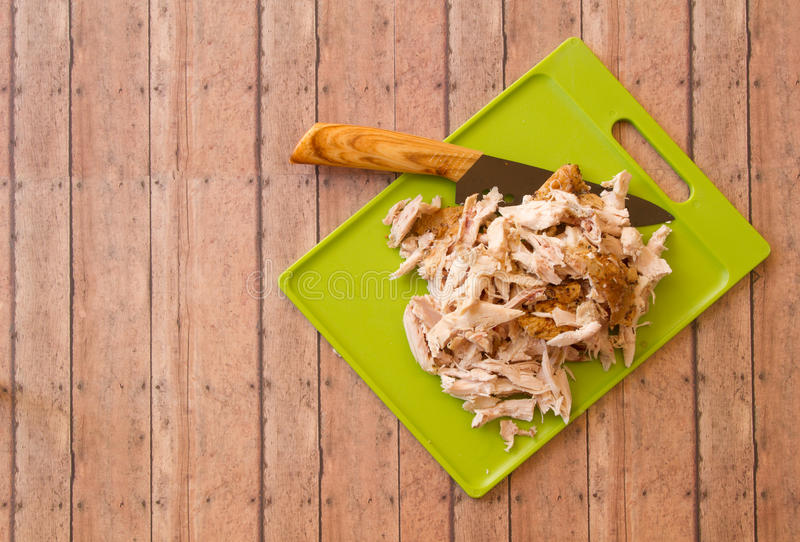 Shredded rotisserie chicken on a green cutting board and carving royalty free stock photo