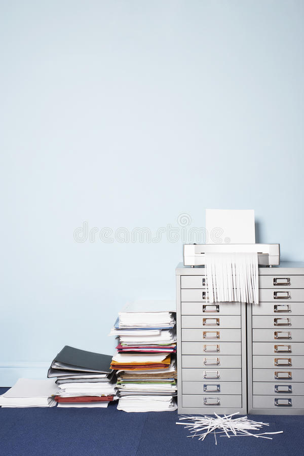 Shredder on file cabinet stack of paperwork on floor in office royalty free stock images