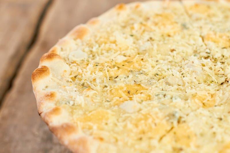 Shredered和熔化乳酪ans香料在比萨外壳,宏观看法 库存照片