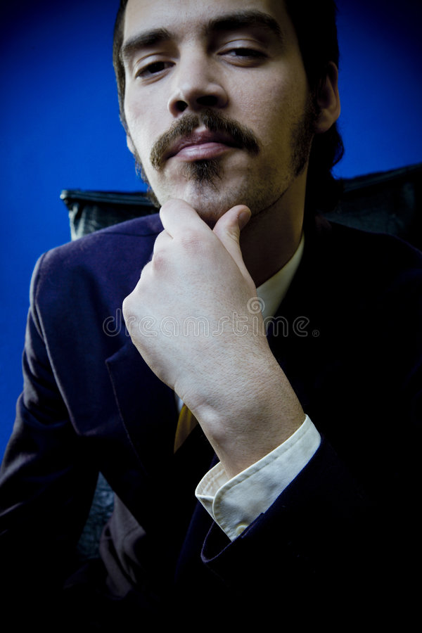 Shrewd, Scheming Businessman. Portrait of a shrewd, scheming, businessman as he sits with one hand to his chin, thinking about his next business venture royalty free stock photo
