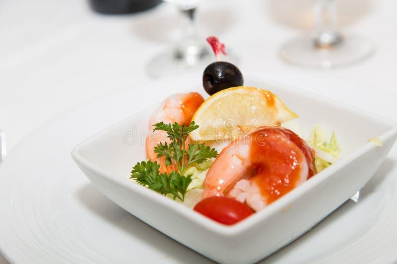 Shrimp Cocktail Garnished with Lemon Wedge and Black Olive stock image