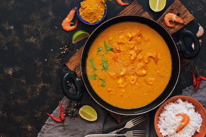 Shrimp in curry sauce with rice on a dark background. Thai Indian dish. Top view, copy space. Asian food. stock photo