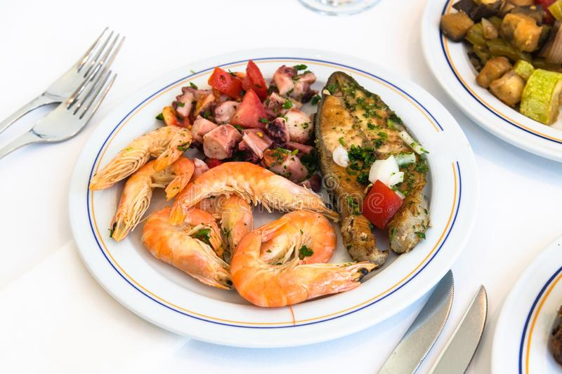 Shrimp, fish and octopus salad on a plate in a cafe royalty free stock photography