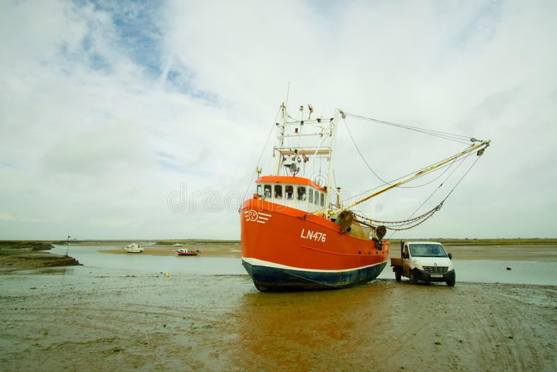Shrimp fishing trawler. Bright orange shrimp trawler called the Catherine Anne in Brancaster staithe harbour in north Norfolk England UK with pick up truck stock photo