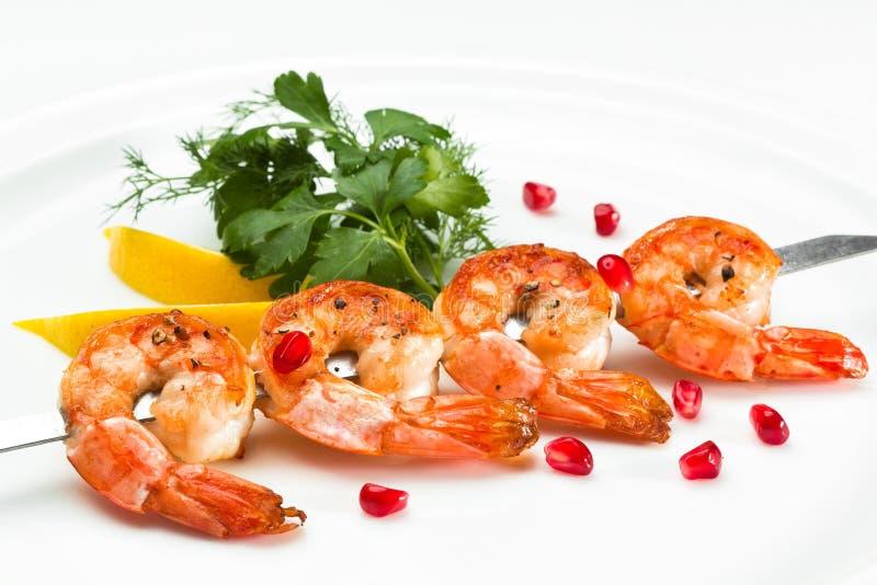 Shrimp kebab skewer served with lemon and parsley on a white background. Prawn starter on a skewer close up stock image