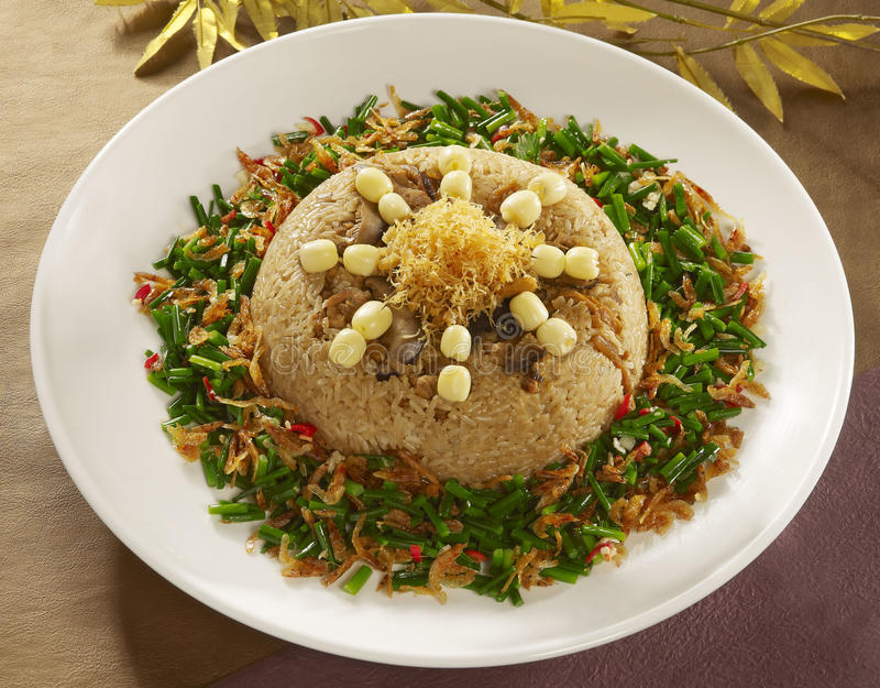 Shrimp lotus seed cakes on fried rice with sauteed onion on whit stock image