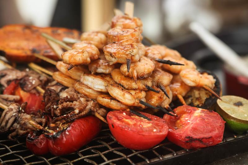 Shrimp and octopus on grill skewers stock photo