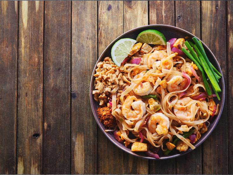 Shrimp pad thai on plate in flat lay composition with copy space atop rustic wooden table. With rule of thirds stock photos