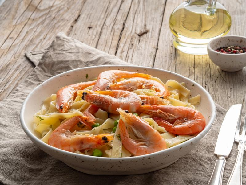 Shrimp, pasta tagliatelle, green peas, dill. White plate on old rustic wooden table, side view, copy space royalty free stock photography
