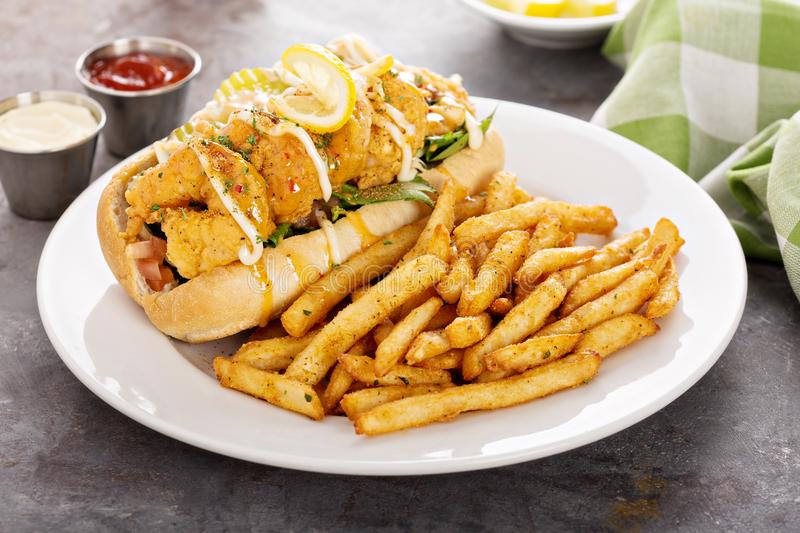 Shrimp po boy sandwich with fries. Served with soda royalty free stock images