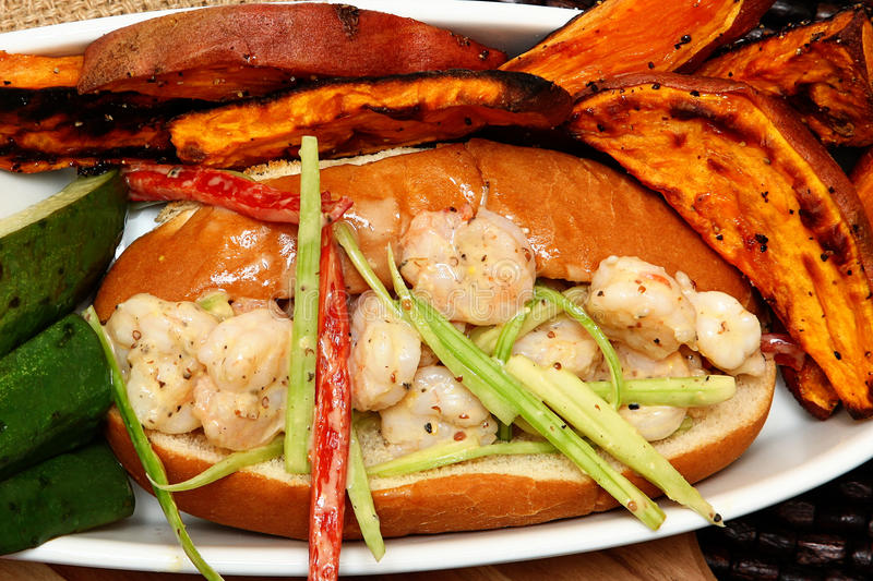 Shrimp Poboy. Hot shrimp poboy with sweet potato fries and pickle spears stock image