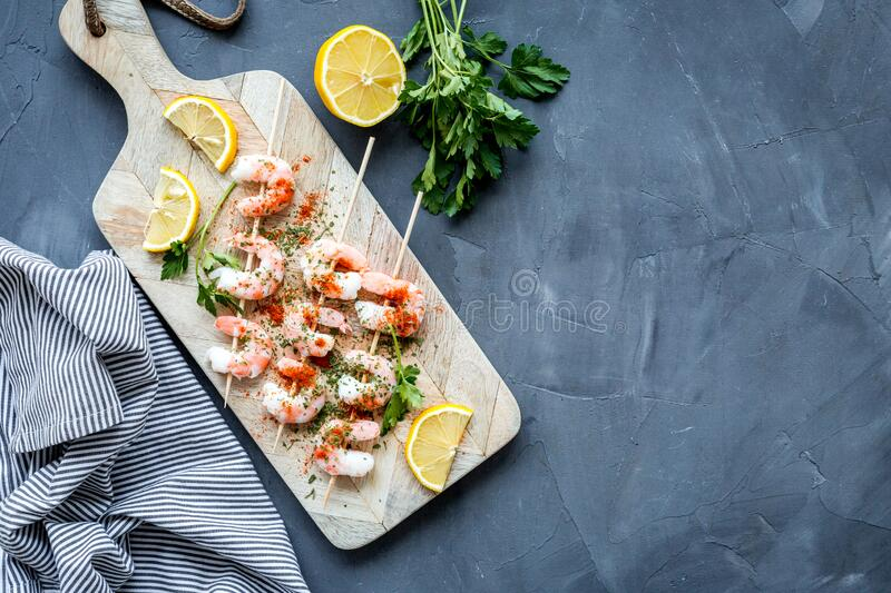 Shrimp skewers - seafood - on grey table top view copy space stock images