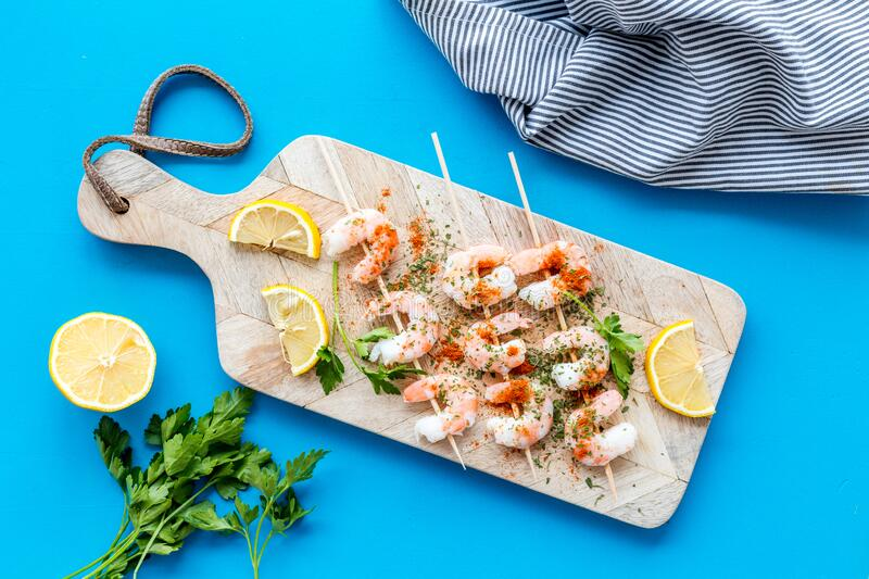 Shrimp skewers - seafood snack - on cutting bioard on blue table top view royalty free stock photos