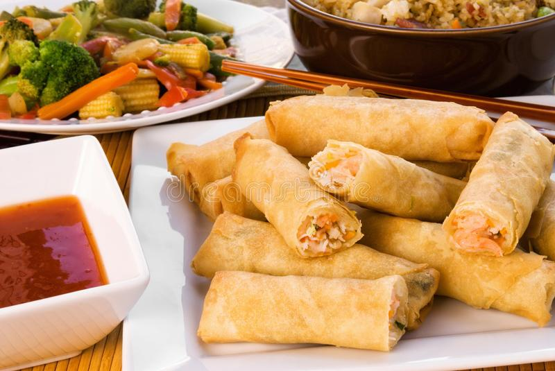 Shrimp Spring Rolls with Stir Fry and Chicken Fried Rice. Shrimp spring rolls served with Asian stir fry and chicken fried rice with vegetables royalty free stock photography