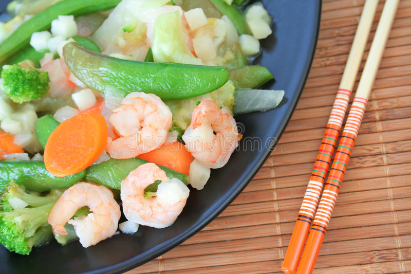 Shrimp Stir Fry. With vegetables, carrots, peas, broccoli, onions, and garlic sauce. Served on a black plate and place on a bamboo place mat with chop sticks stock photos