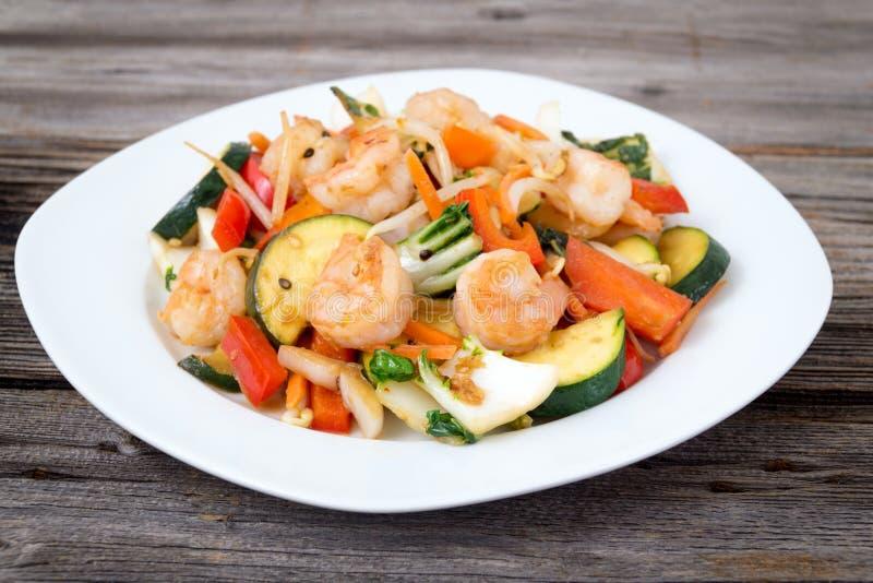Shrimp stir fry with vegetables dinner. Shrimp stir fry with vegetables over wood background stock photos